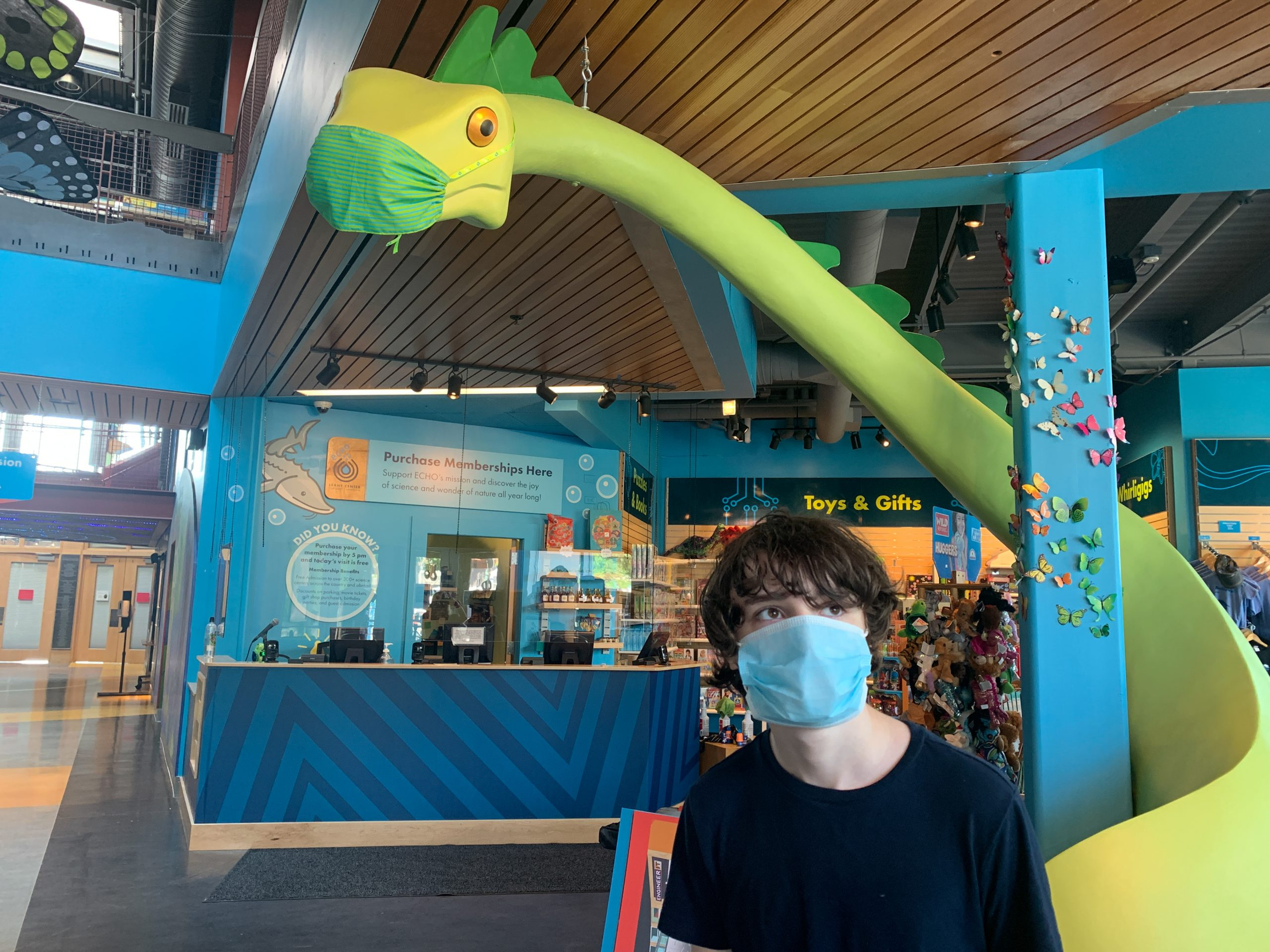 Child with mask on next to the Gift Shop's champ with a mask on