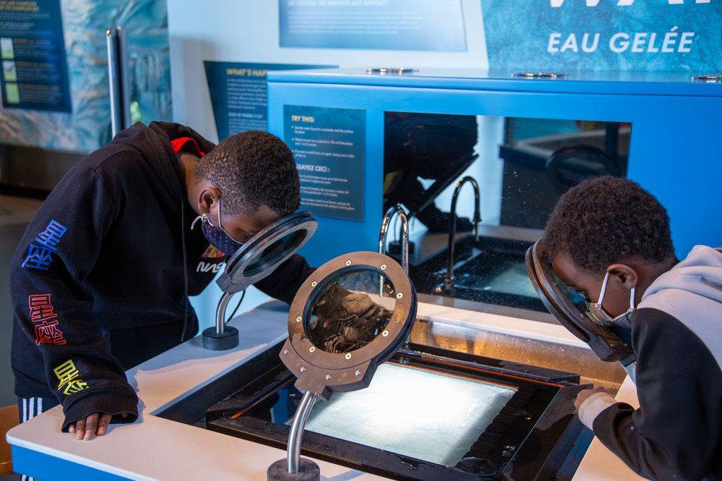 Kids looking through polarizing magnifying glasses on freezing water exhibit