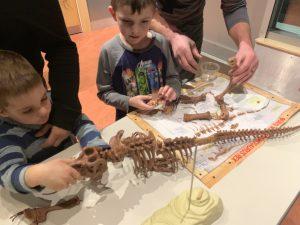 kids putting together a dinosaur skeleton