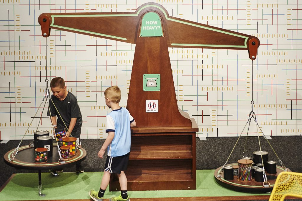 Shows a large oversized scale with kids putting items on it to balance it in the Measurement Rules exhibit.