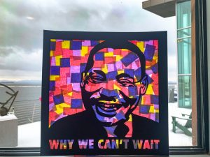 "Black laser cut image of MLK with the words ""Why We Can't Wait"" and behind it a collage of colored paper, hung up on a window with Lake Champlain in the distance"