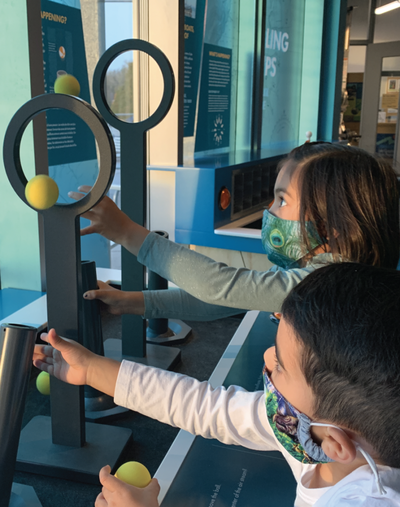 Families testing the Bernoulli blower--air that blows yellow balls and you control the direction to move the balls through hoops--in Awesome Forces exhibit at ECHO