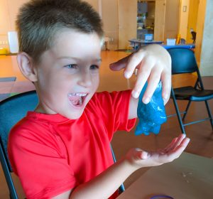 Child in red shirt holding blue slime