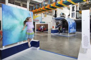 Girl jumping in front of a blue green background at an exhibit in the Human Plus exhibitions