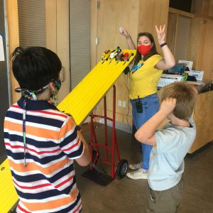 ECHO Educator about to let lego cars down a bright yellow racing track with kid campers looking on