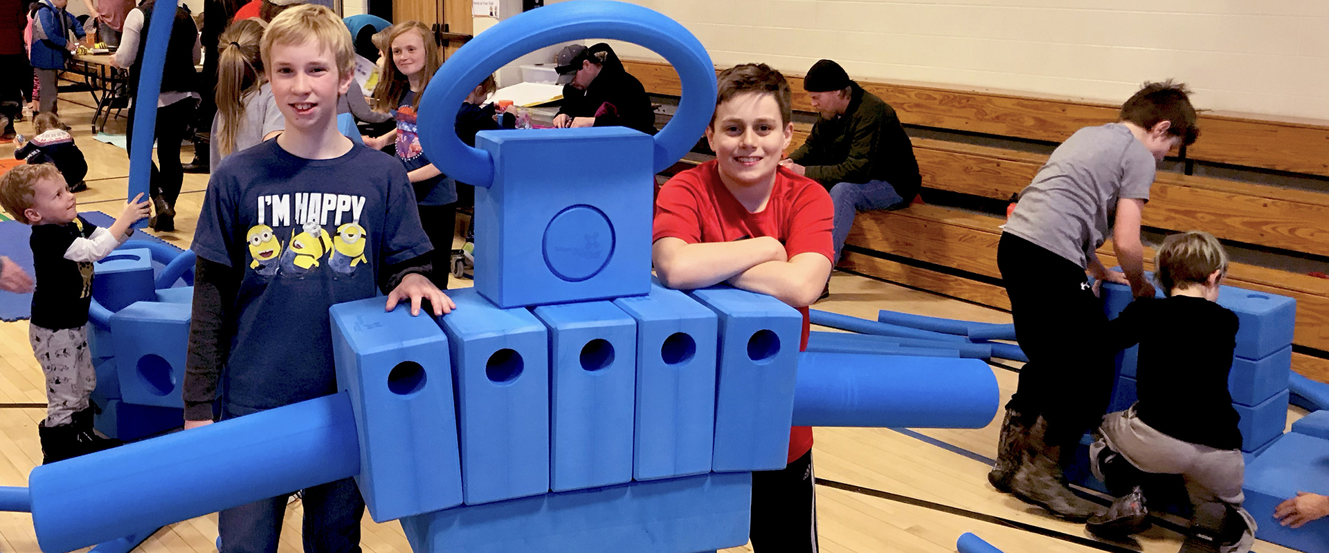 Kids at school building an oversized blue robot with blue blocks