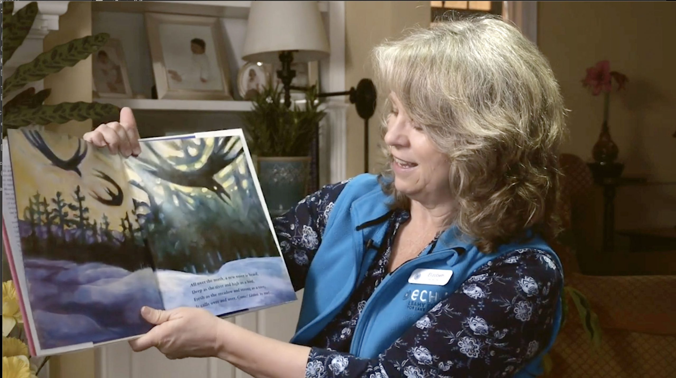 Elizabeth with blonde hair and blue ECHO Vest holds up the book she is reading about spring.