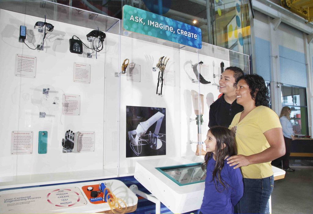 Family with an adult male, adult female, young girl, are looking at an exhibit wall filled with inventions for the body.