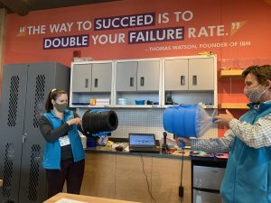 One female ECHO intern in a blue vest aiming an air cannon at a male ECHO educator in a blue vest with an air cannon ready to blow air at the intern. Both people are in front of an orange wall and white cabinets in the Engineer It space.